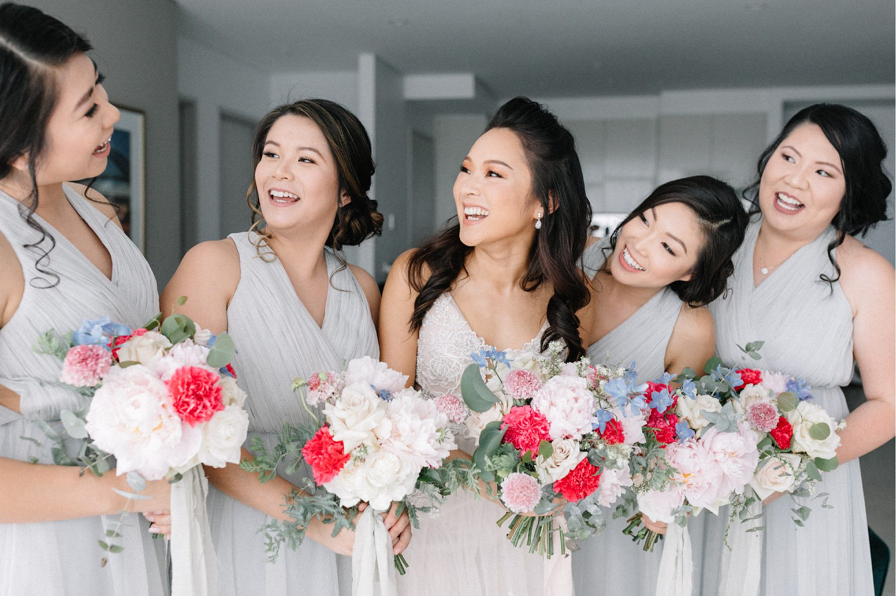 bride and bridesmaids laughing while holding wedding flowers